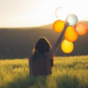 Frau im Feld hält Luftballons