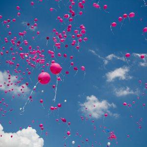 Viele rosafarbene Luftballons fliegen in den Himmel