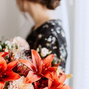 Trauernde Frau mit Blumenstrauß